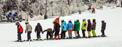 儿童` s高山滑雪学校 五颜六色的滑雪设备的辅导员和儿童学生 库存图片
