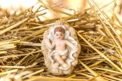 婴儿耶稣在秸杆床上的诞生装饰反对glowi的 库存图片