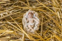 婴儿耶稣在秸杆床上的诞生装饰  免版税库存照片