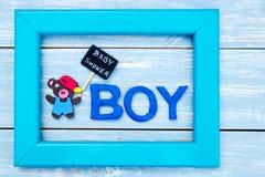 婴儿送礼会-男孩-负担与黑板签到在蓝色木背景的框架 库存图片