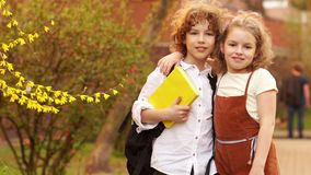 兄弟和姐妹、男孩和女孩拥抱以一棵开花的春天树为背景 天知识 回到 股票视频