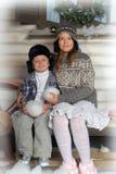 兄弟和姐妹一条长凳的在房子前面在冬天 免版税库存图片