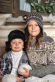 兄弟和姐妹一条长凳的在房子前面在冬天 免版税图库摄影