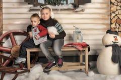 兄弟和姐妹一条长凳的在房子前面在冬天 免版税库存照片