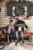 兄弟和姐妹一条长凳的在房子前面在冬天 库存照片