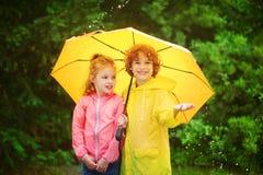 兄弟和姐妹一起站立在一把大黄色伞下 免版税库存图片