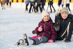 兄弟和姐妹一起跌倒了,当滑冰时 免版税库存照片