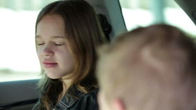 兄弟和姐妹使用用巧克力兔子的汽车的后座的 影视素材