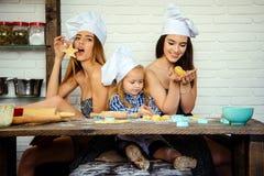 兄弟和姐妹准备曲奇饼的厨师帽子的 库存照片