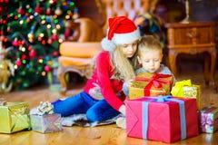 兄弟和姐妹圣诞老人项目帽子的坐地板并且选择礼物,以欢乐圣诞节为背景 库存照片