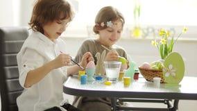 兄弟和姐妹在厨房里在家绘复活节彩蛋 他们集中 刷子和油漆,儿童` s 股票录像