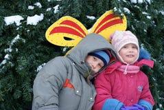 兄弟和姐妹在圣诞节杉树附近 图库摄影