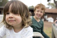 兄弟和姐妹在坐在桌上的公园 图库摄影