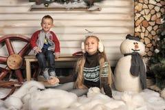 兄弟和姐妹在房子前面在冬天 图库摄影