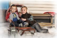 兄弟和姐妹在房子前面在冬天 免版税库存图片