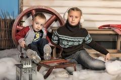 兄弟和姐妹在房子前面在冬天 免版税图库摄影