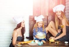 兄弟和姐妹在桌上使用厨房用具 免版税库存照片