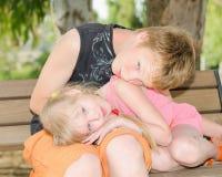 兄弟和姐妹在长凳一起clured在公园 免版税库存图片