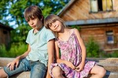 兄弟和姐妹坐一条长凳在村庄 库存图片