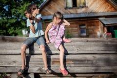 兄弟和姐妹坐一条长凳在村庄 库存照片