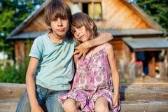 兄弟和姐妹坐一条长凳在村庄 免版税库存照片