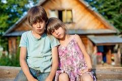 兄弟和姐妹坐一条长凳在村庄 免版税库存图片