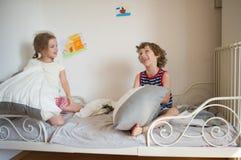 兄弟和姐妹坐床在卧室 免版税库存图片