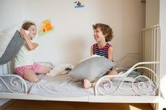 兄弟和姐妹坐床在卧室 免版税库存照片