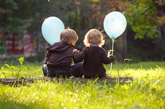 兄弟和姐妹坐树干,拿着蓝色气球 免版税库存照片