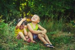 兄弟和姐妹坐草在夏天下下雨 免版税图库摄影