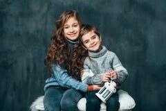 兄弟和姐妹微笑着并且拥抱 免版税库存照片