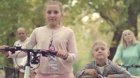 兄弟和姐妹有自行车的在秋天停放 在有自行车的背景父母 循环的公园 股票录像