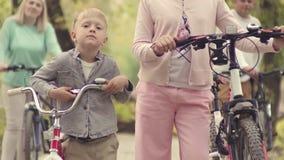 兄弟和姐妹有自行车的在秋天停放 在有自行车的背景父母 循环的公园 影视素材