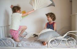 兄弟和姐妹由在一张床上的枕头安排了战斗在卧室 免版税库存照片