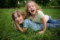兄弟和姐妹获得在绿色草坪的乐趣 库存照片