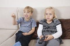 兄弟和姐妹观看的电视 免版税库存照片