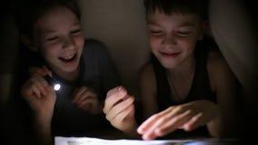 兄弟和姐妹读了一本书在有一个手电的一条毯子下在一个暗室在晚上 孩子使用 股票视频