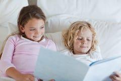 兄弟和姐妹读取河床时间故事 库存图片