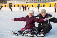 兄弟和姐妹跌倒了,当滑冰和获得乐趣时 库存图片