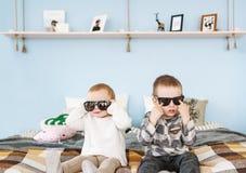兄弟和姐妹画象太阳镜的在家坐床 库存照片