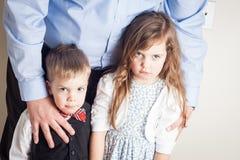 兄弟和姐妹画象由父亲举行了 免版税库存图片
