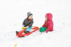 兄弟和姐妹sledding在一个多雪的冬天环境美化 图库摄影
