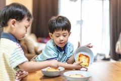 兄弟在去前教育享用他们喜爱的煎蛋卷 库存照片