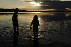 兄弟在湖的水中日落的 免版税库存图片