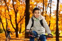 兄弟在秋天公园骑一辆自行车 库存图片