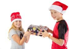 兄弟姐妹交换一个圣诞节礼物 图库摄影