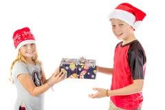 兄弟姐妹交换一个圣诞节礼物 库存图片