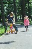 兄弟姐妹儿童愉快的使用的标记比赛通过跑和乘坐哄骗三轮车 库存图片
