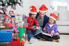 兄弟姐妹和父亲阅读书由圣诞节 免版税库存照片