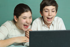 兄弟姐妹手表在膝上型计算机的喜剧英尺长度 免版税图库摄影